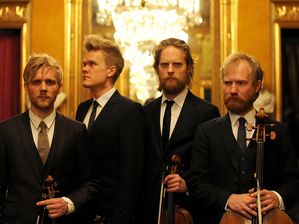 The Danish String Quartet hold their instruments. Two look at the camera, two look away. Behind are lit chandeliers.