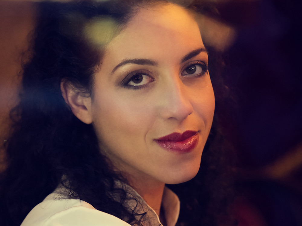 Close-up of pianist Beatrice Rana looking directly at the camera with a slight smile. She wears a white collared shirt.