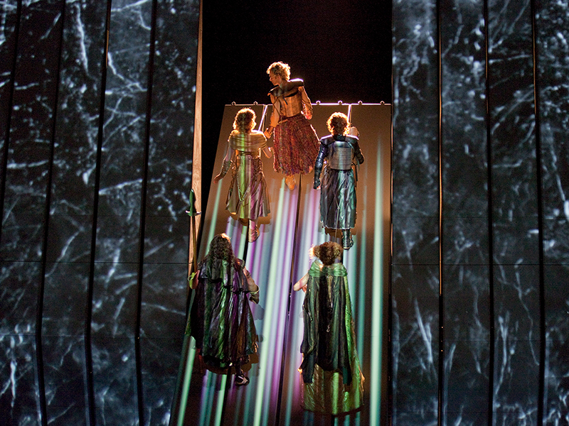Five futures in bright, metallic costumes ascend vertically on shimmering set.