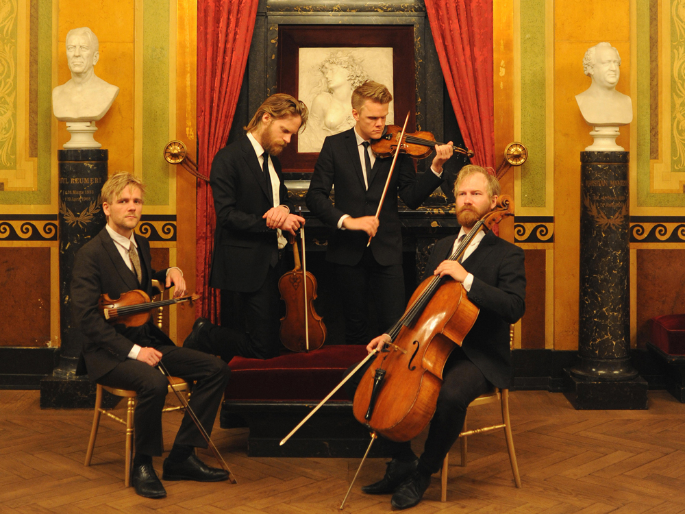 The Danish String Quartet hold their instruments. Two are seated, two standing. Each look in different directions.