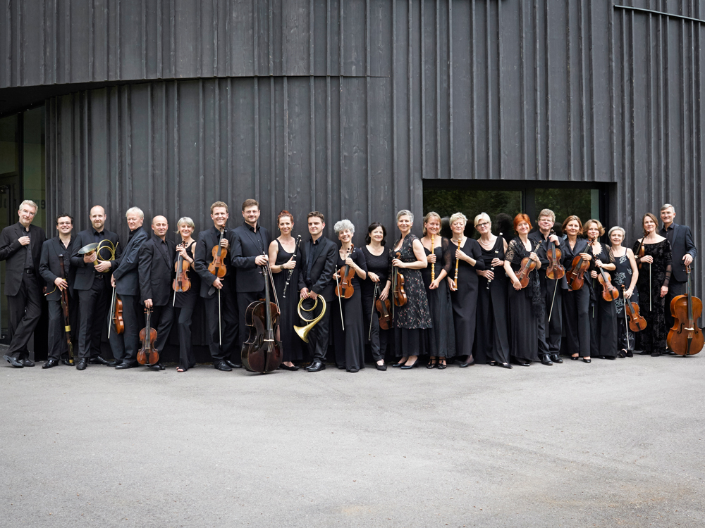 Twenty-three musicians wearing black, holding their instruments, stand against a black building façade.