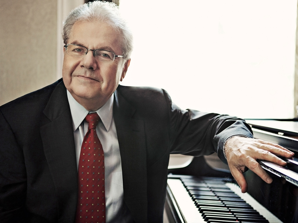 Emanuel Ax sits with arm resting on a piano, looking at the camera, wearing a black suit, white shirt, and red tie.