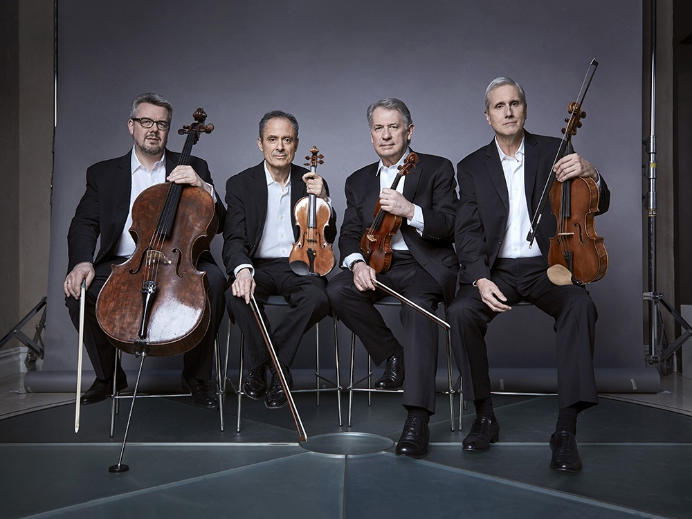 Emerson String Quartet, wearing black suits and white formal shirts, sit on stools holding instruments. Left to right: Cello, two violins, viola.