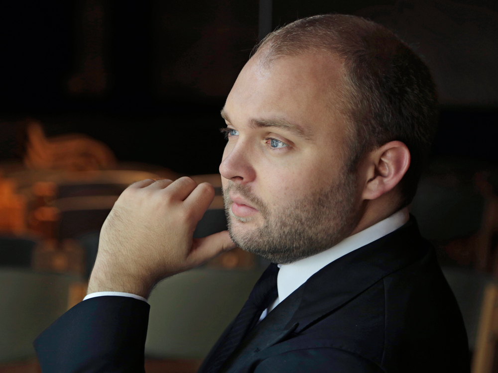 Tenor Matthew Swenson, wearing dark suit and tie, stares to the side with his hand toward his chin.
