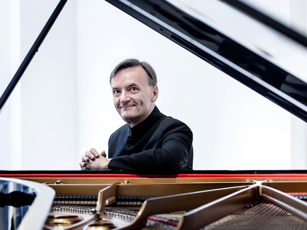Stephen Hough, wearing all black, rests his elbow with folded hands on an open piano. He looks directly at the camera.