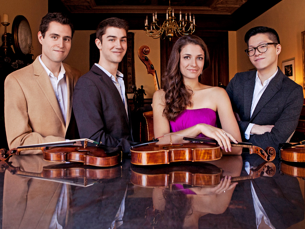 The Dover Quartet leans on a piano, three violins lay in front of them.