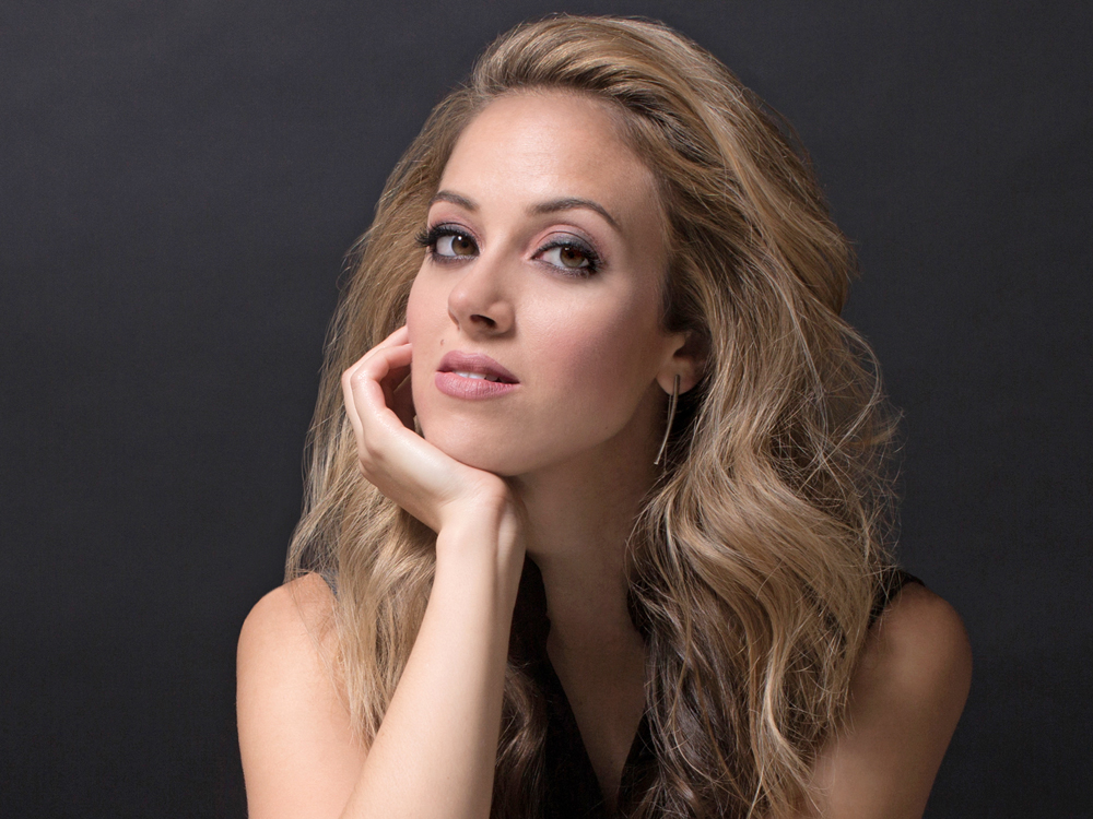 Profile of Soprano Lauren Snouffer; long blonde hair, wearing a black sleeveless top, with her chin on her hand.