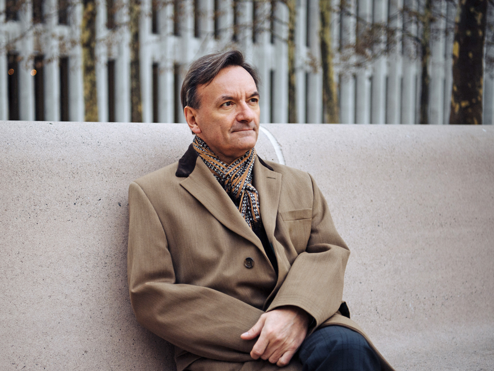 Stephen Hough sits outdoors on a concrete bench wearing a tan jacket and scarf.