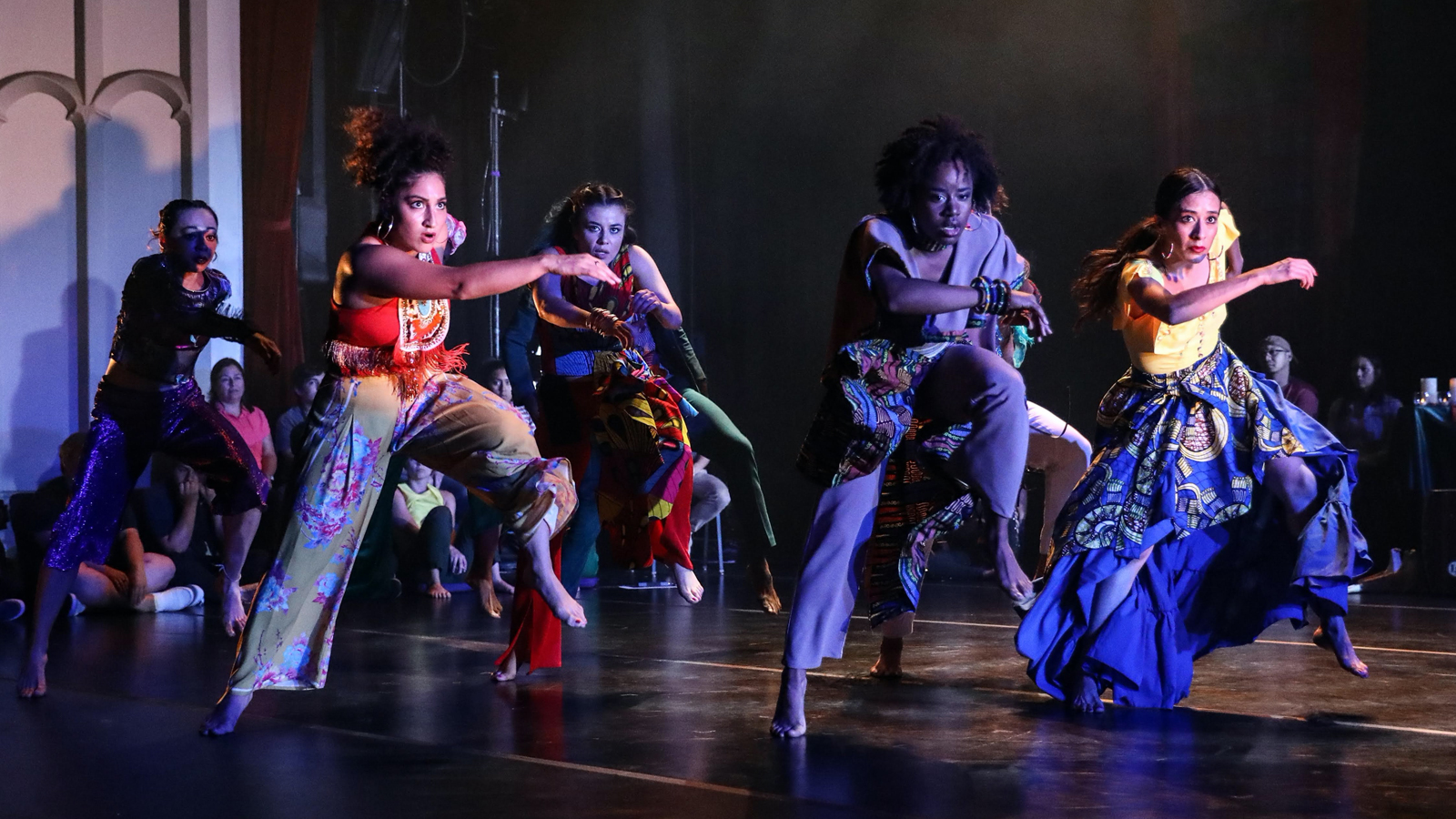 Group of six dancers barefoot wearing colorful loose clothing on a dancefloor leaning forward, left legs lifted with right arms extended across their bodies.