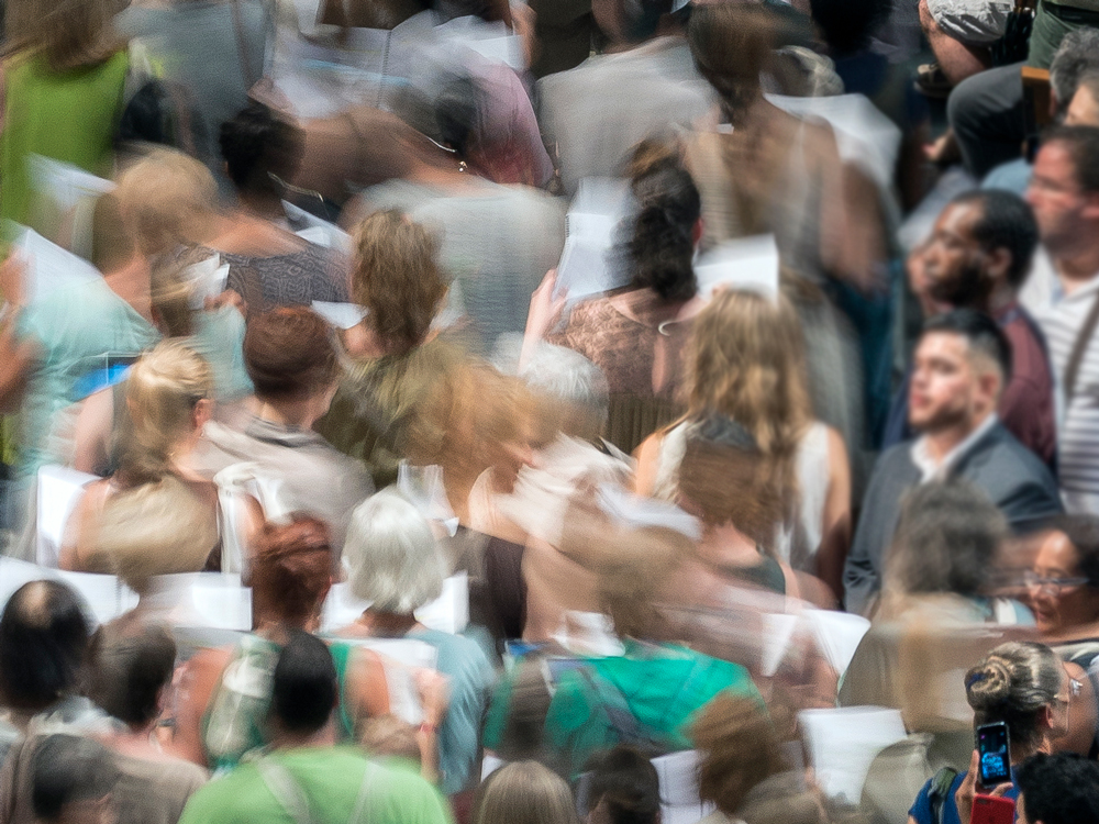 People gathered in a crowded space. The image is blurred, conveying movement.
