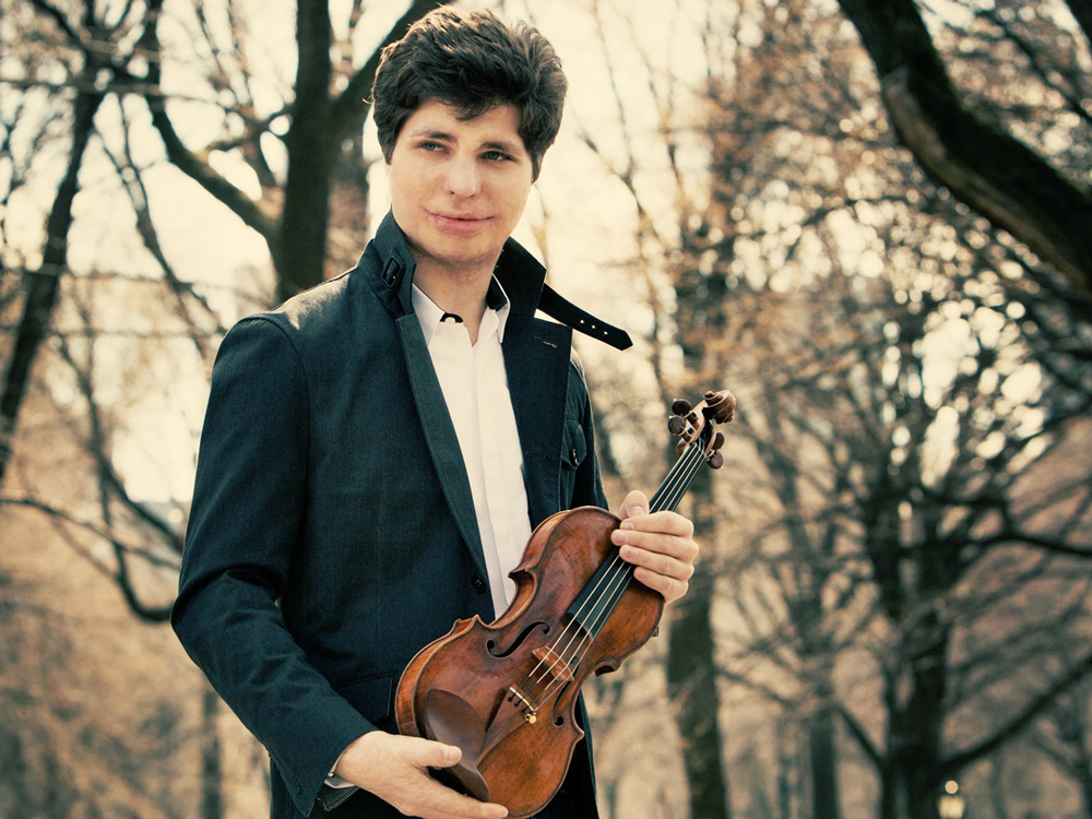 Violinist, Augustin Hadelich, holds a violin across his torso and glances to the right, against bare trees in the background.