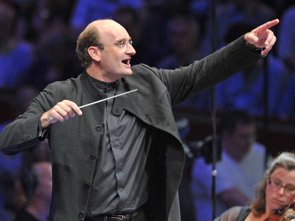 Conductor Andrew Manze stands with one arm outstretched, holding a baton with musicians and audience members in the background.