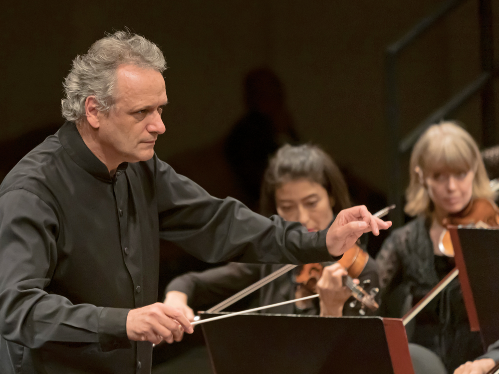 Conductor Louis Langrée holds a baton, arms outstretched and gazing intently. Two musicians play in the background.