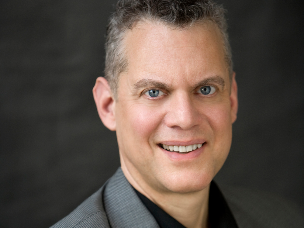 Close up of pianist Steven Blier, wearing a gray suit and black shirt, smiling at the camera.