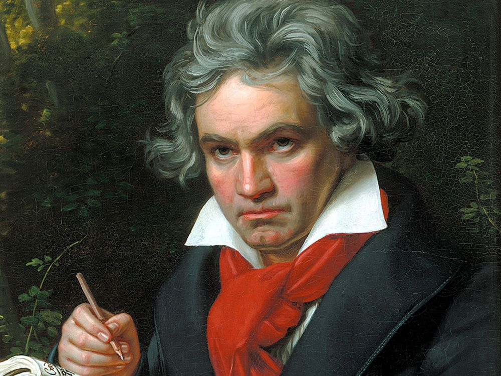 Painting of Beethoven holding a pen. He is wearing a black jacket, with a large red scarf tied over a white top with a wide collar.