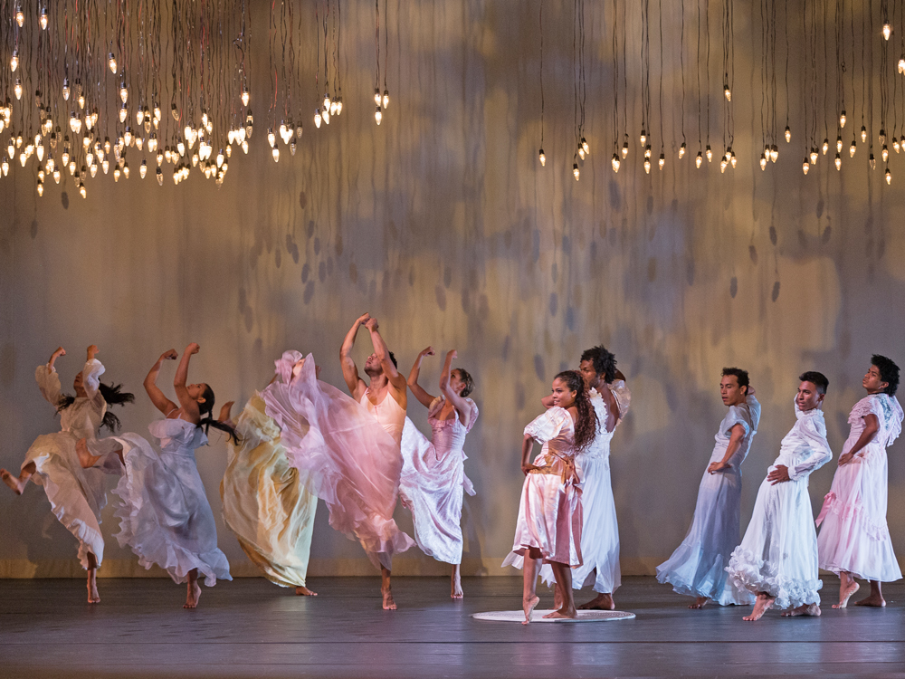 Ten dancers on stage with pastel-colored dresses. They extend their feet, five with arms raised, five with hands on hips.