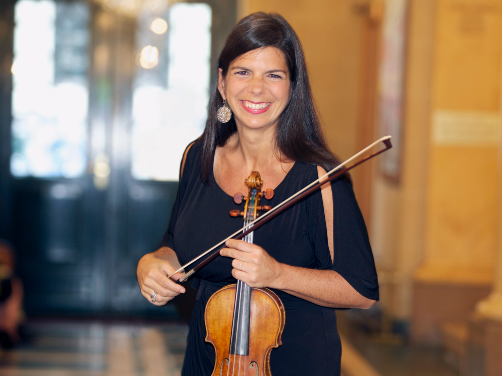 Pamela Frank holds a violin and bow. She wears a black dress and smiles at the camera.