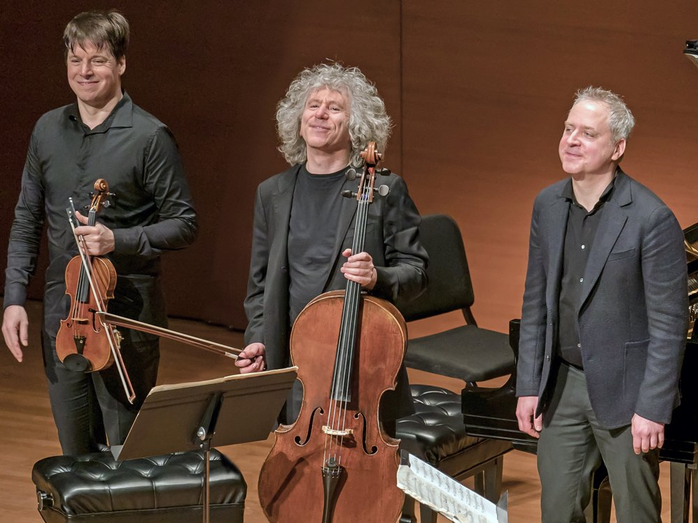 Joshua Bell, Jeremy Denk, and Steven Isserlis wearing all black, standing and smiling. Bell and Denk hold their instruments.