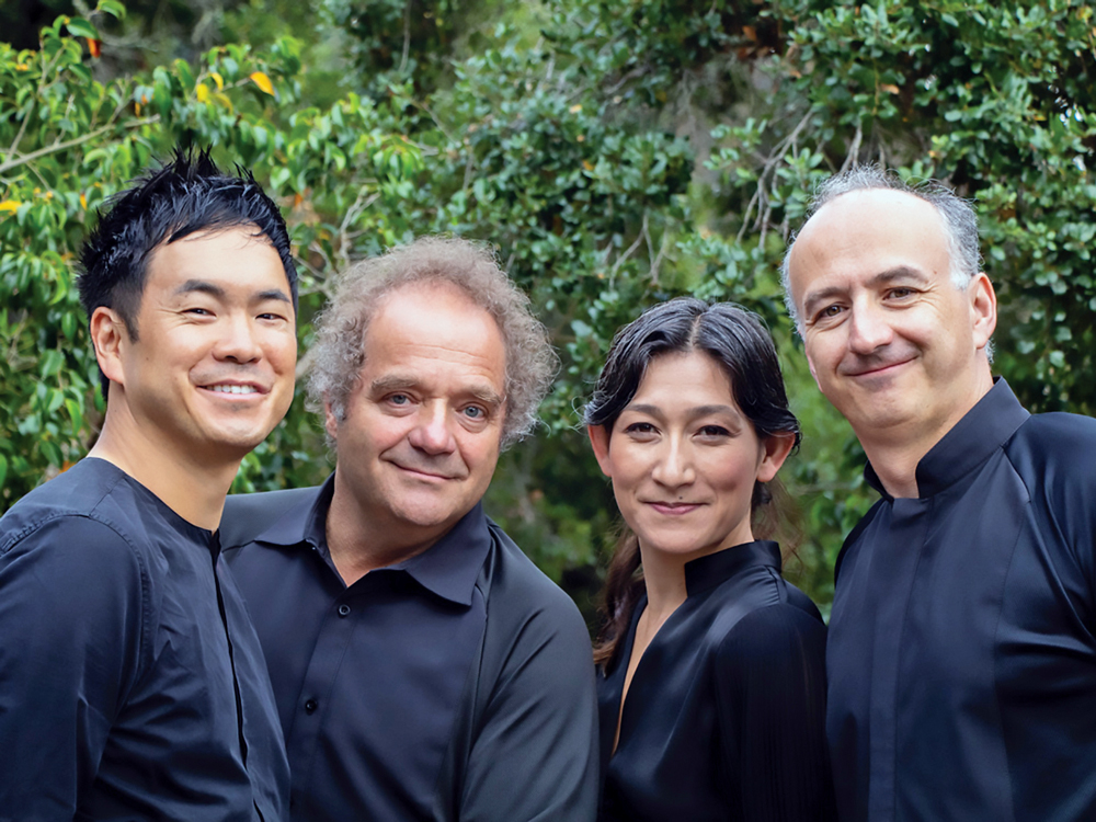 Members of Takacs Quartet, visible from the waist up, stand close together, smiling at the camera, with a green, outdoor backdrop.