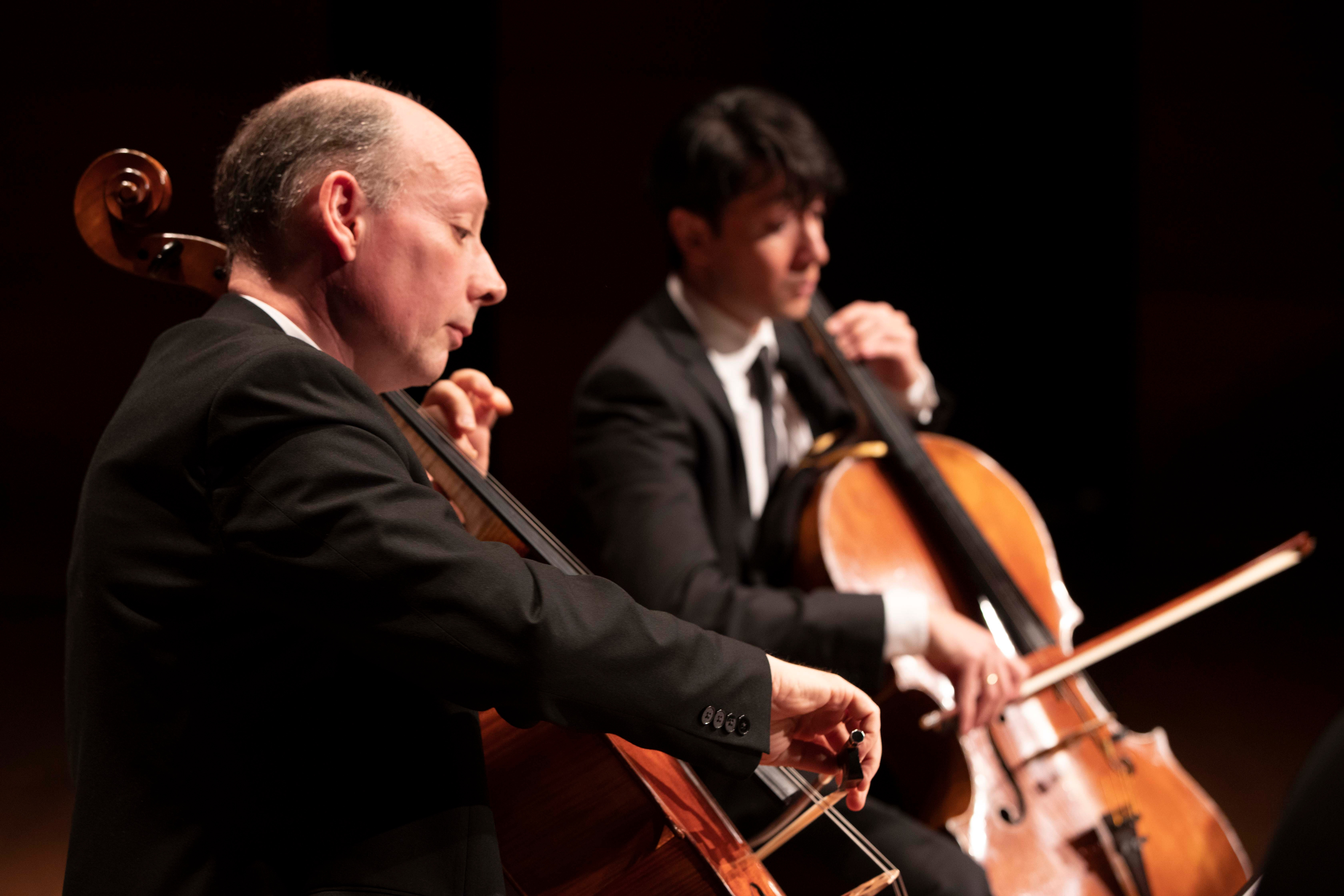 Two cellists, one in foreground, one in blurred background, wearing suits perform on darkened stage.