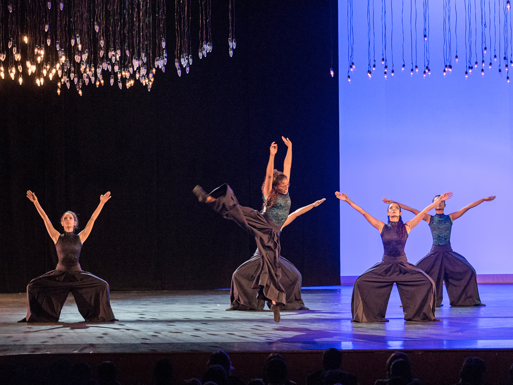 Four dancers in the background squat with outstretched hands. Dancer in foreground stands on tiptoe with leg horizontal.