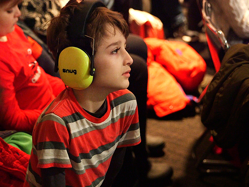 Audience watches performance, including young person in audience wearing bright yellow headphones.