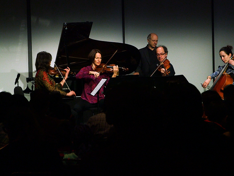 Three violin players and a cellist perform on stage, facing each other, with conductor and host Ivan Fischer watching. The backs of heads of audience members are in foreground.