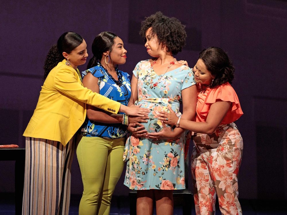 Three women gather around a fourth woman who is pregnant. They touch her belly while smiling and looking fondly at her.