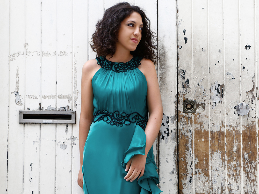 Pianist Beatrice Rana wears a sleeveless turquoise dress with black trimming, standing against a weathered white wooden door.
