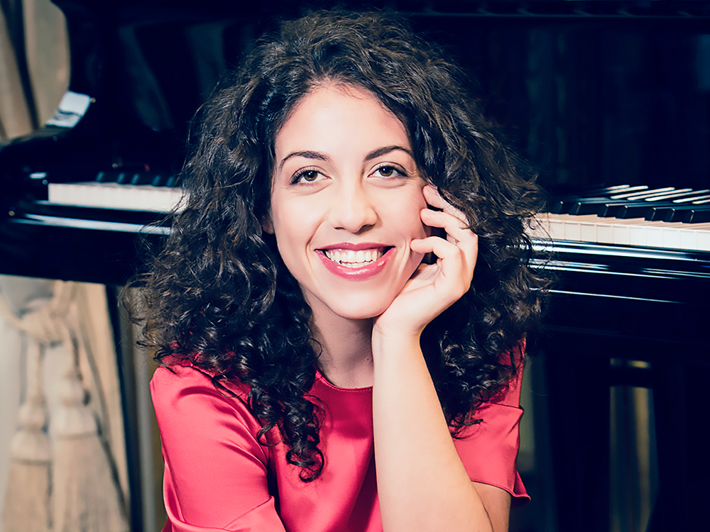 Pianist Beatrice Rana smiles brightly at camera, with chin resting on hand, sitting in front of piano.