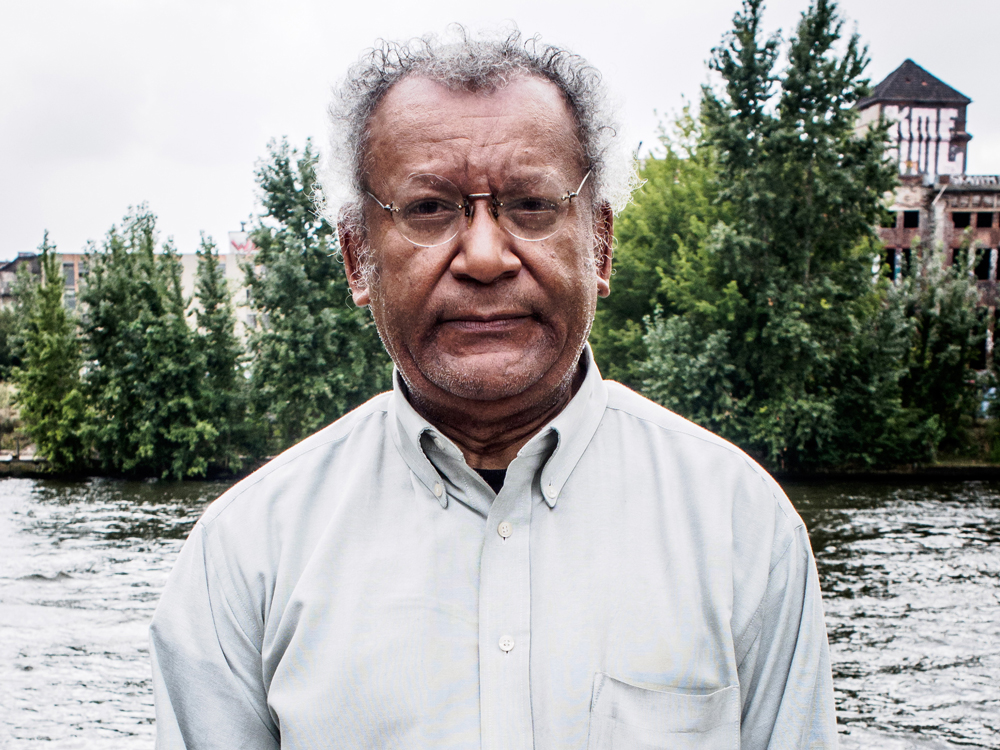 Anthony Braxton, wearing a white shirt, stands in front of a river with trees and a building in the background.