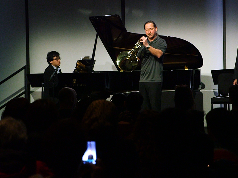 Pianist and horn player perform, with conductor and host Ivan Fischer watching on stage.  The backs of heads of audience members are in foreground.