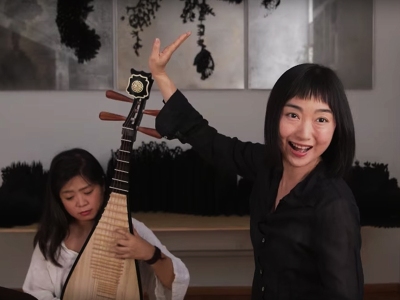 Singer with raised arm and mouth open in song performs with pipa player in background.