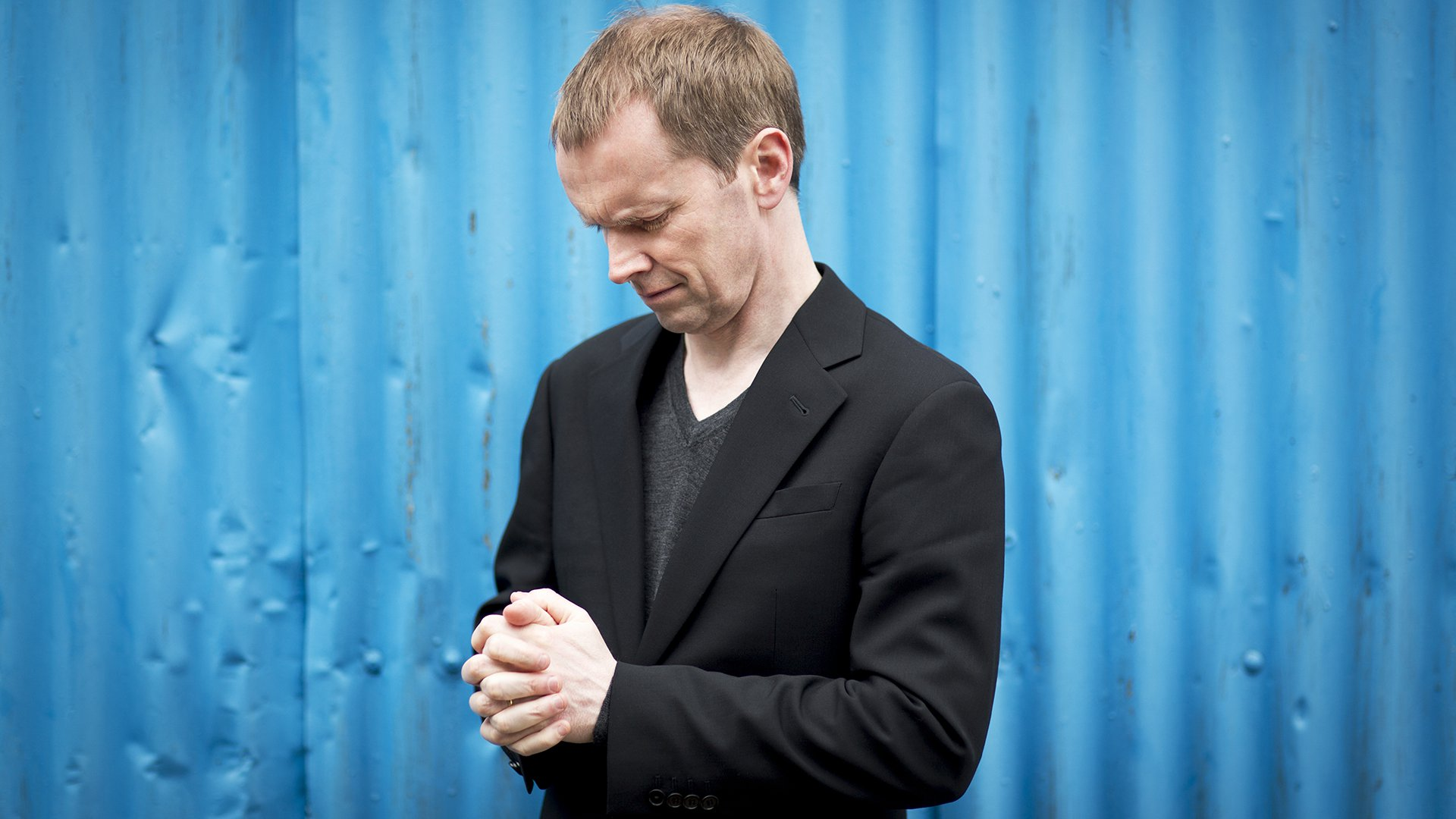 Steven Osborne is wearing a black jacket and black top, hands clasped, looking down contemplating. Blue corrugated metal background.