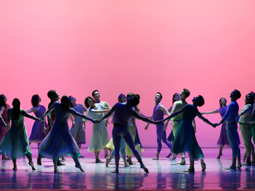 Dancers in dresses and body suits hold hands in concentric circles on a stage lit in pink and purple tones.