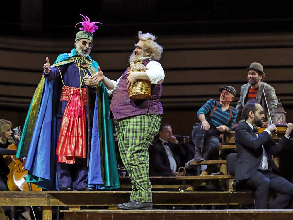 Two colorfully dressed performers extend their hands. In the background musicians play and two performers sit on benches.