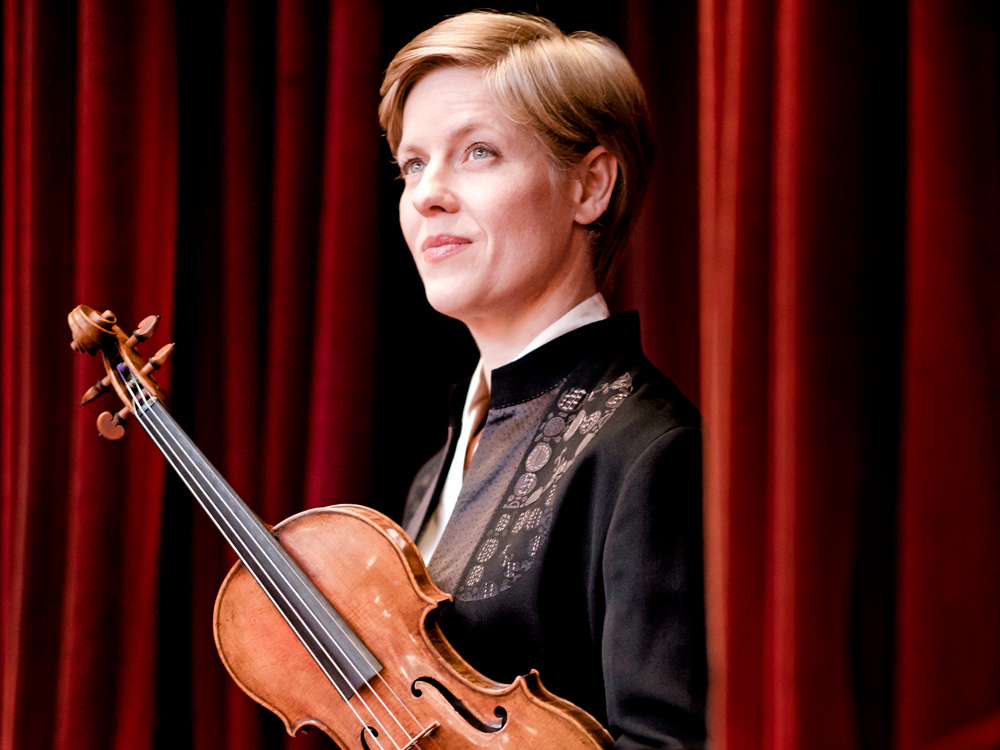 Isabelle Faust holds a violin and wears a white collared shirt and black blazer, standing in front of a red velvet curtain.