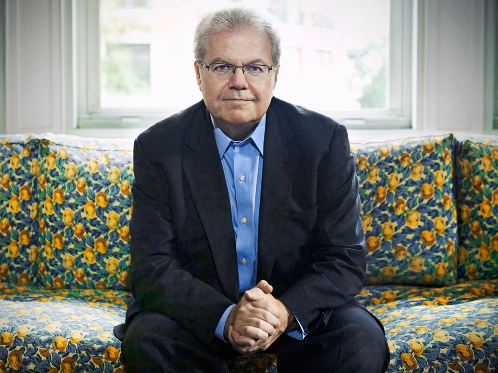 Emanuel Ax sits on a blue and yellow patterned couch clasping his hands and looking at the camera.