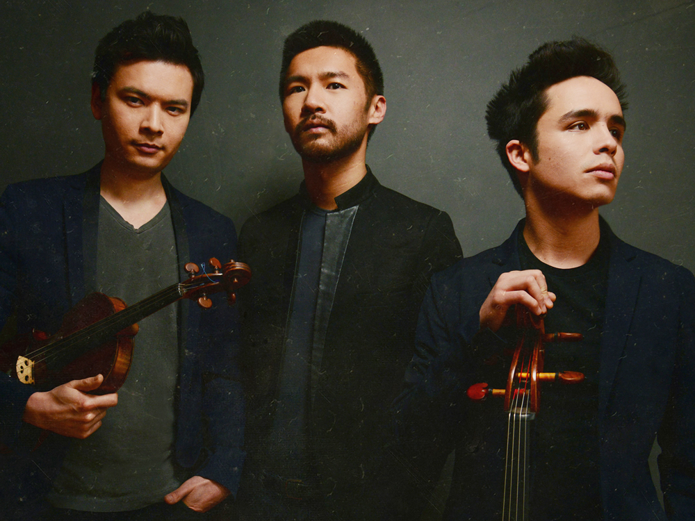 The Junction Trio stands against a black background, each looking in different directions. Two hold instruments.