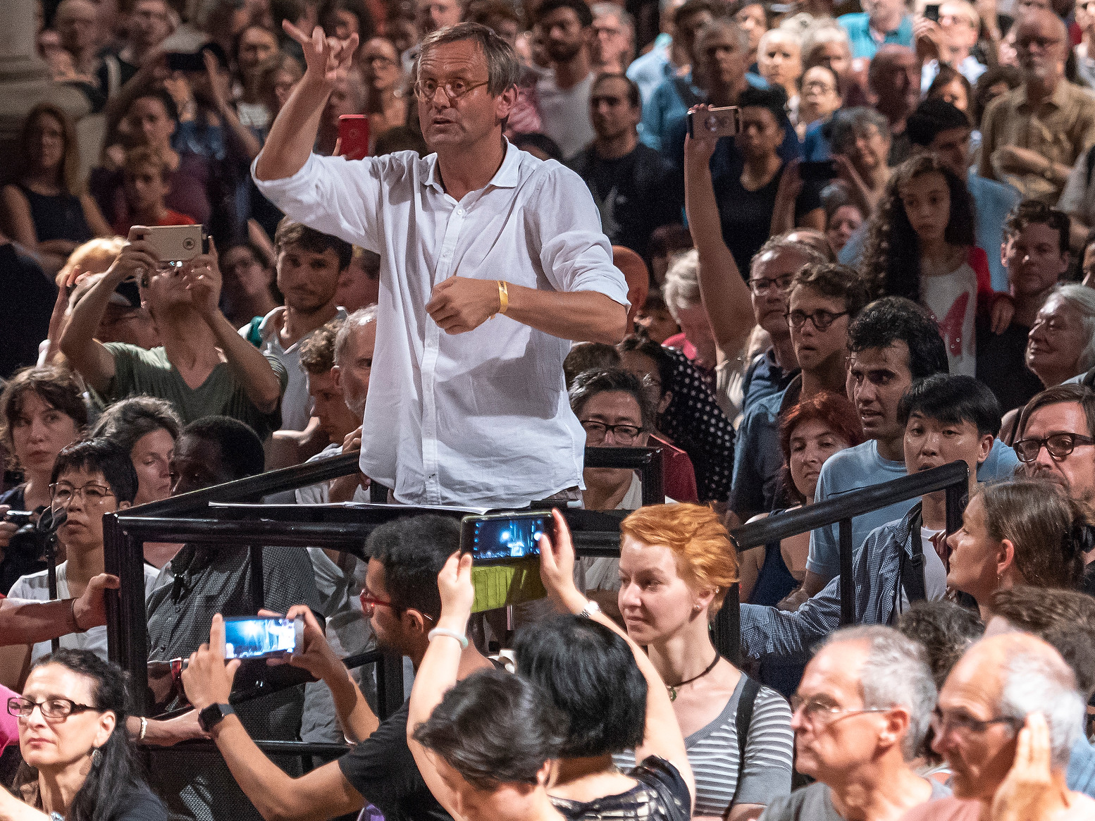 Conductor Simon Halsey stands on a platform with raised arms, surrounded by people, some holding phones to take photos.