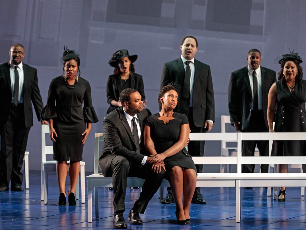 Couple sits on a bench, the woman turns her face away from the man, they clasp hands. Six others sing in the background.
