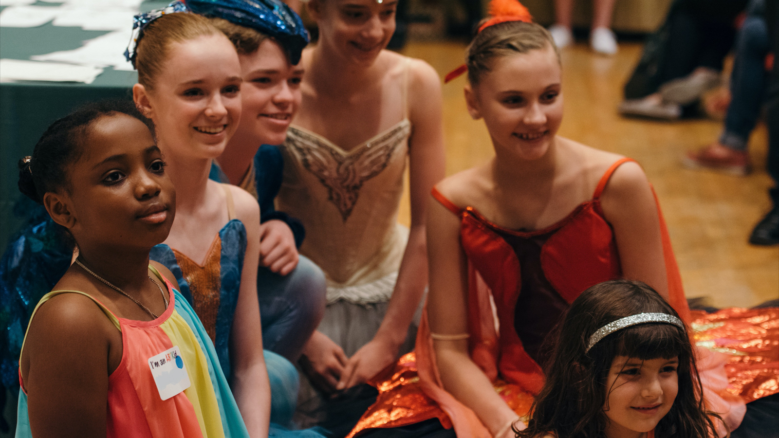 Six young dancers, four in full ballet costume, sit closely together and smile off-camera.