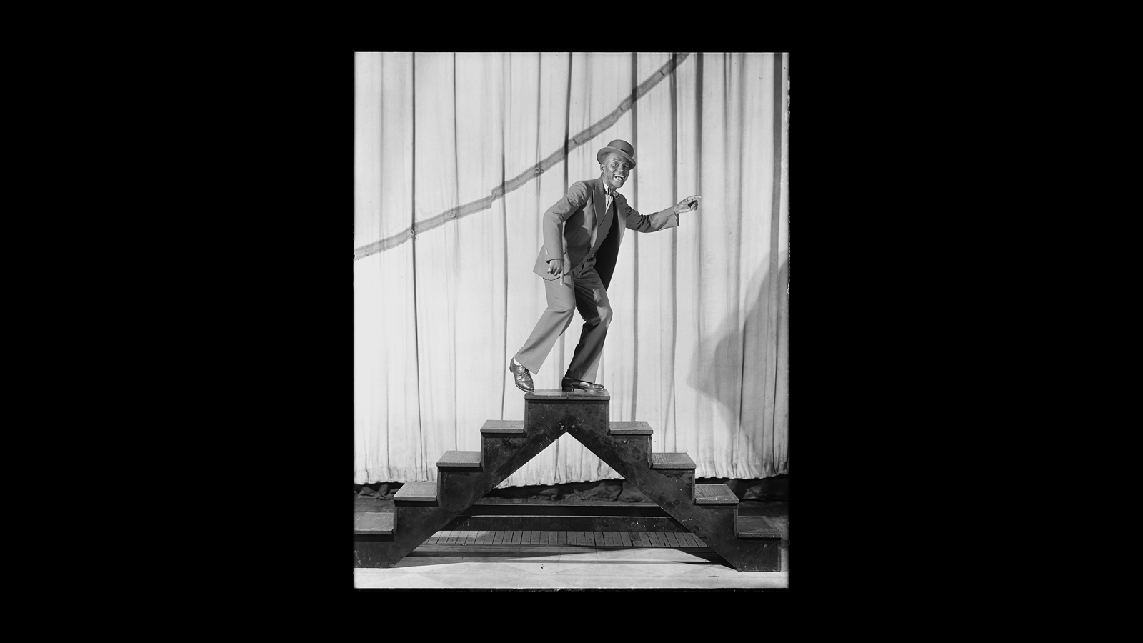 Bill Robinson (Bojangles), wearing a suit and hat, one arm outstretched, with smile, poses at top of a platform with five steps on each side.