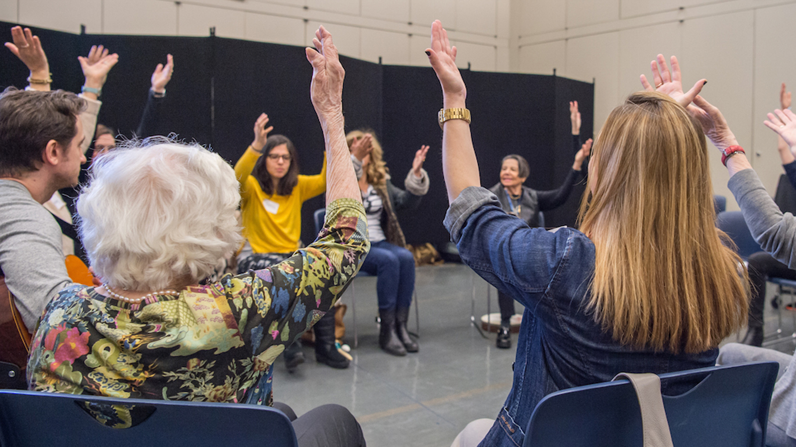 A dozen people, most older adults, sitting in a circle raise their arms in the air. One person holds a guitar.