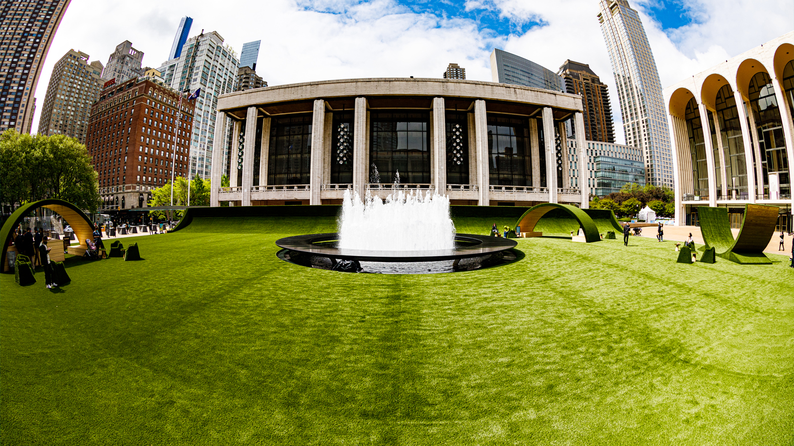 Fish-eye lens view of The GREEN, lawn extending across Lincoln Center's campus with fountain in center, set against Metropolitan Opera House and skyline.